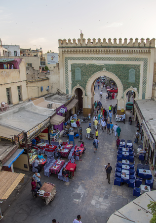 bab: FES, MOROCCO - SEPTEMBER 14, 2014: Unidentified people at Bab Bou Jeloud gate (Blue Gate) at Fes Medina, Morocco. Medina in Fes is listed as a UNESCO World Heritage Site from 1981.