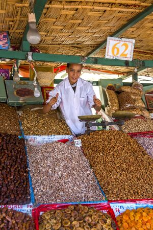 dry fruit: MARRAKESH, MOROCCO - SEPTEMBER 12, 2014: Unidentified boy selling dry fruits on the market in Marrakesh, Morocco.  Morocco is one of the largest dry fruit producers in the world. Editorial