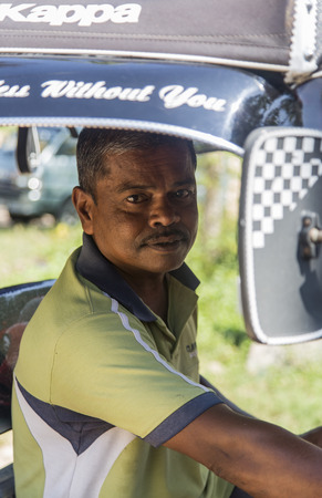 bajaj: UNAWATUNA, SRI LANKA - JANUARY 23, 2014: Unidentified driver on tuk-tuk on the street of Unawatuna. Most tuk-tuks in Sri Lanka are a slightly modified Indian Bajaj model, imported from India. Editorial