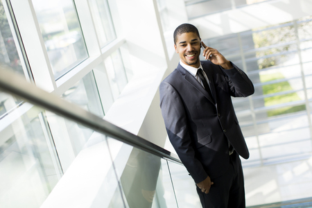 african man: Handsome young black man with mobile phone in the office
