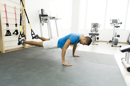 african man: Man does crossfit push ups with trx fitness straps in the gyms studio