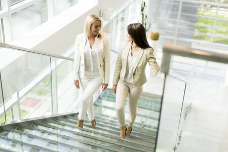corporate building: Pretty young women on stairs in the office