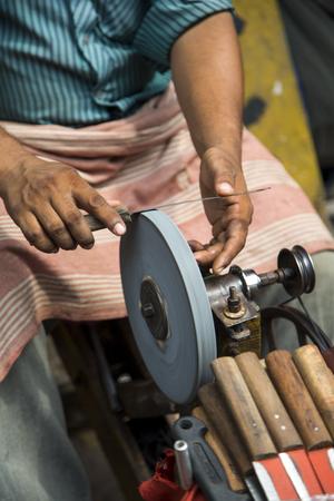 sharpening process: Man sharpening a knive Stock Photo