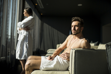 masculinity: Man with a towel sitting in a room