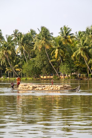 backwaters: KERALA, INDIA - OCTOBER 16, 2015: Unindetified men at backwaters in Kerala, India. The backwaters are an extensive network of 41 west flowing interlocking rivers, lakes and canals that center around Alleppey, Kumarakom and Punnamada. Editorial