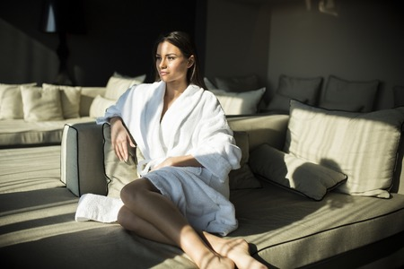 house robes: Woman in a bathrobe sitting in the sunlighted room