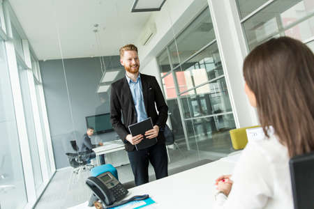 front desk: Businessman standing in front of the desk in the office Stock Photo