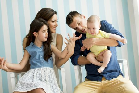 family  room: Young family with two daughters in the room Stock Photo