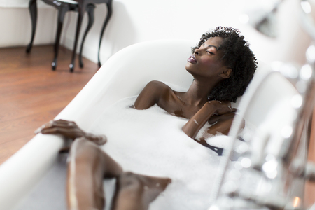 mujer ba�andose: Woman bathing in a tub full of foam