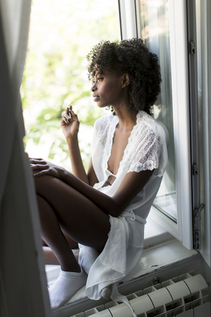 unhealthy thoughts: Woman sitting and smoking on the window