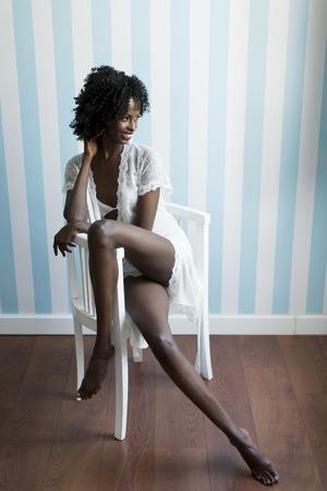 modelos negras: mujer afroamericana joven que se sienta en la silla
