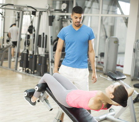 Woman training with a trainer in the gym