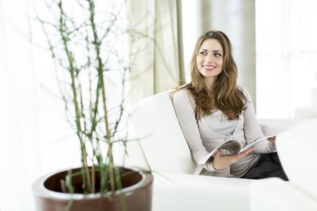 Woman sitting and reading a magazine at home Stock Photo