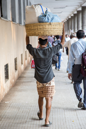 ancient times: MUMBAI, INDIA - OCTOBER 9, 2015: Unidentified man carryng weight on his head. People have carried burdens balanced on top of the head since ancient times, usually to do daily work.