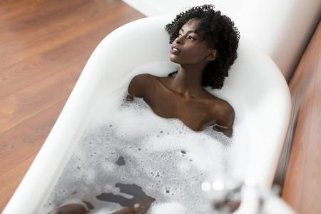 personas banandose: Mujer que se baña en una bañera llena de espuma Foto de archivo