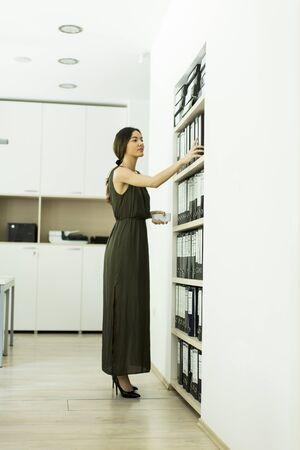 carpeta: Mujer joven que trabaja en la oficina moderna