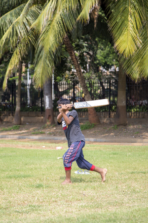 british man: MUMBAI, INDIA - OCTOBER 10, 2015: Man playing cricket in the central park at Mumbai. Cricket is the most popular sport in India. History of cricket in India is based on the existence and development of the British Raj.