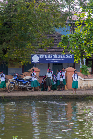 backwaters: KERALA, INDIA - OCTOBER 16, 2015: Unindetified schoolgirls at backwaters in Kerala, India. The backwaters are an extensive network of 41 west flowing interlocking rivers, lakes and canals that center around Alleppey, Kumarakom and Punnamada.