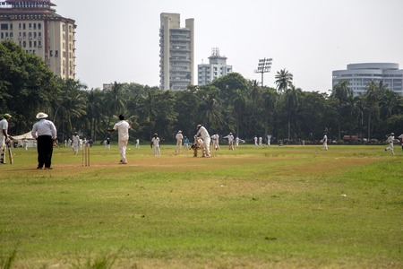 existence: MUMBAI, INDIA - OCTOBER 10, 2015: People playing cricket in the central park at Mumbai, India. Cricket is the most popular sport in India. History of cricket in India is based on the existence and development of the British Raj.