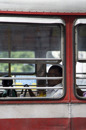 mode transport: MUMBAI, INDIA - OCTOBER 10, 2015: Unidentified man in the bus. Buses take up over 90% of public transport in Indian cities and serve as a cheap and convenient mode of transport for all classes of society.