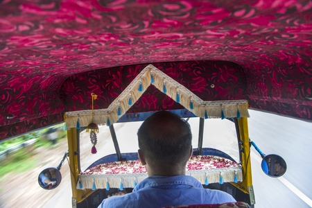 three wheeler: VARKALA, INDIA - OCTOBER 18, 2015: Unidentified driver of auto rickshaw in Varkala. Auto rickshaws are used in cities and towns for short distances and they provide cheap and efficient transportation. Editorial