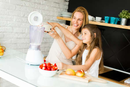 blending: Mother and daughter blending smoothie from fresh fruits in the modern kitchen Stock Photo
