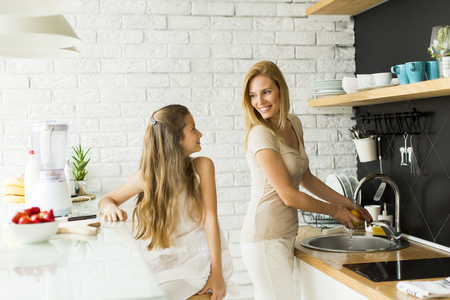 Mother and a daughter preparing fruits for smoothie