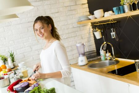 cutting vegetables: Pretty young woman cutting vegetables in the modern kitchen
