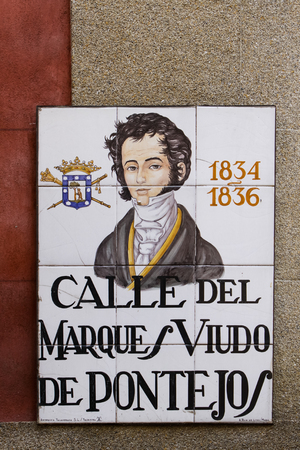 depict: MADRID, SPAIN - MARCH 13, 2016: Closeup of the street sign in Madrid. They are hand-painted ceramic tiles typically composed within 9 or 12 tiles. They depict the name of the alley or street, as well as illustrations that indicate special meanings. Editorial