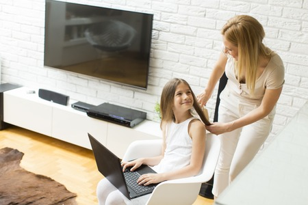 combing: Mother combing a daughter while on the laptop at home