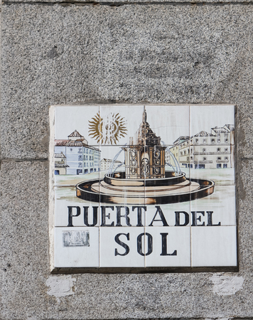 12 13: MADRID, SPAIN - MARCH 13, 2016: Closeup of the street sign. Street signs in Madrid are hand-painted ceramic tiles typically composed within 9 or 12 tiles. They depict the name of the alley or street, as well as illustrations that indicate special meanings