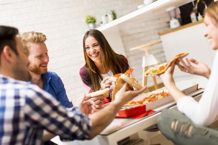 Grupo de amigos comiendo pizza juntos en casa