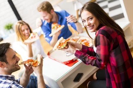 Groep vrienden die pizza thuis samen eten