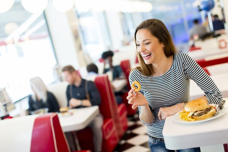 fast food restaurant: View of the young woman eating in the diner