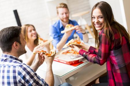 Groep vrienden het eten van pizza samen thuis