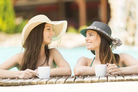bathe mug: Two women drinking coffee in the pool Stock Photo