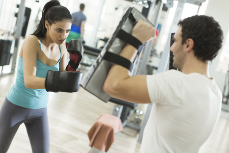 female boxer: Pretty young woman boxing in the gym with trainer Stock Photo