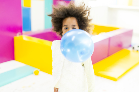 powerfully: African little girl inflates blue  balloon Stock Photo