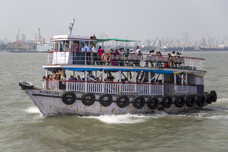 government services: MUMBAI, INDIA - OCTOBER 11, 2015: Unidentified people on a ferry. Water transport in Mumbai consists mostly of ferries. Services are provided by both government agencies as well as private partners.