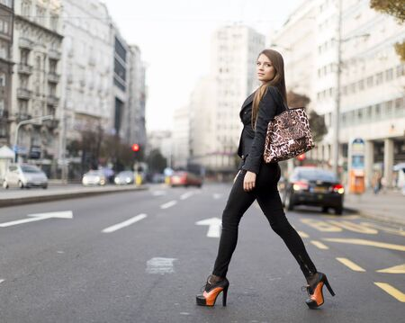 rich people: View at attractive young woman walking on a street Stock Photo