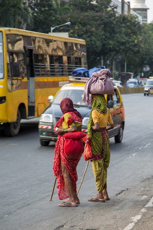 MUMBAI, INDIA - OCTOBER 9, 2015: Unidentified women carrying weights in Mumbai. People have carried burdens balanced on top of the head since ancient times, usually to do daily work. Stock Photo - 58471351