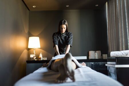 massaged: Beautiful young and healthy woman having her shoulder and body massaged by a professional masseur at a spa center