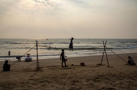 entertainers: ANJUNA, INDIA - OCTOBER 14, 2015: Unidentified Goan Girl on a tightrope at the Anjuna Beach. Small groups of entertainers travel along the coast and give free shows for tourists on the beach.