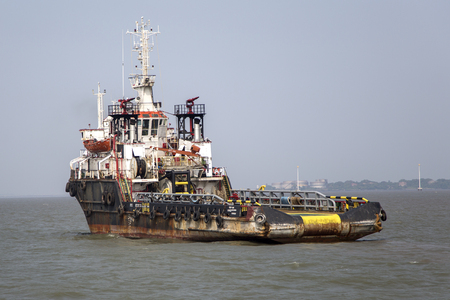 indirectly: MUMBAI, INDIA - OCTOBER 11, 2015: Industrial ship in the waters of Mumbai. The port and shipping industry employs many residents directly and indirectly.