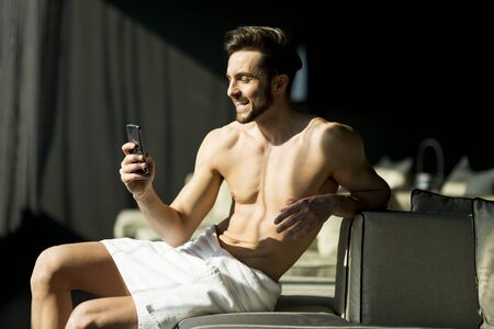 masculinity: Man wrapped in a towel sitting in a room and holding a phone Stock Photo