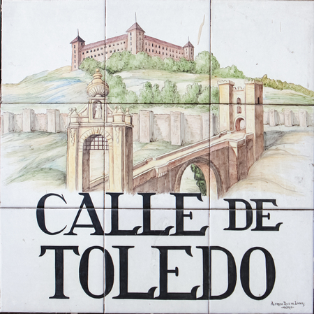 depict: Closeup of the street sign. Street signs in Madrid are hand-painted ceramic tiles typically composed within 9 or 12 tiles. They depict the name of the alley or street.