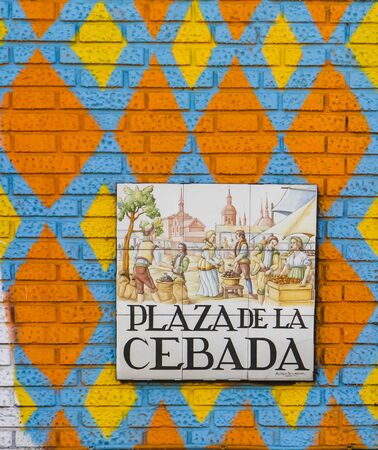 depict: MADRID, SPAIN - MARCH 13, 2016 : Closeup of the street sign. Street signs in Madrid are hand-painted ceramic tiles typically composed within 9 or 12 tiles. They depict the name of the alley or street. Stock Photo