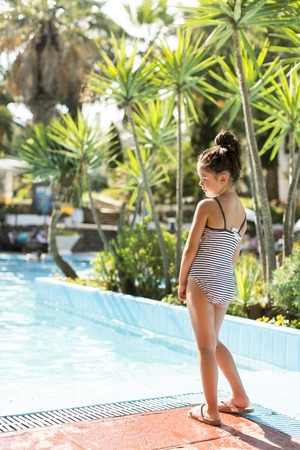 waterpool: Cute little girl standing by the swimming pool Stock Photo