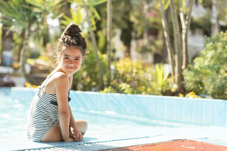skimpy: Cute little girl sitting by the swimming pool