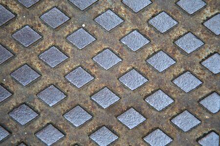 sewage: Texture of the metal manhole cover of street sewage shaft Stock Photo